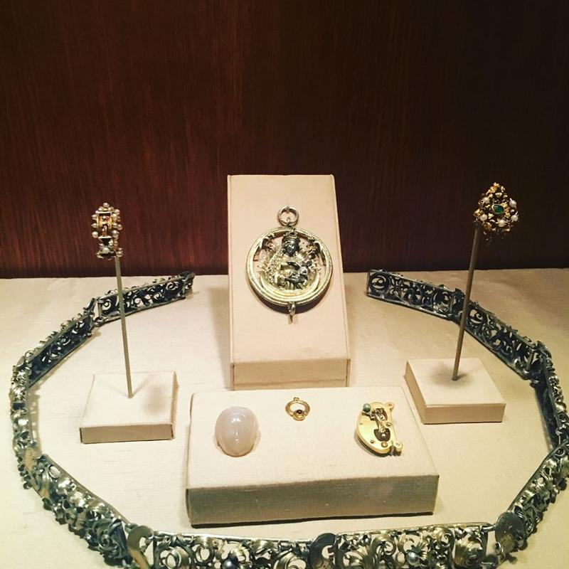 "Jewelry from the Treasury Room; a dress or hat ornament, along with a locket & broach in the shape of the letter ""E,"" possibly the first initial of its owner."